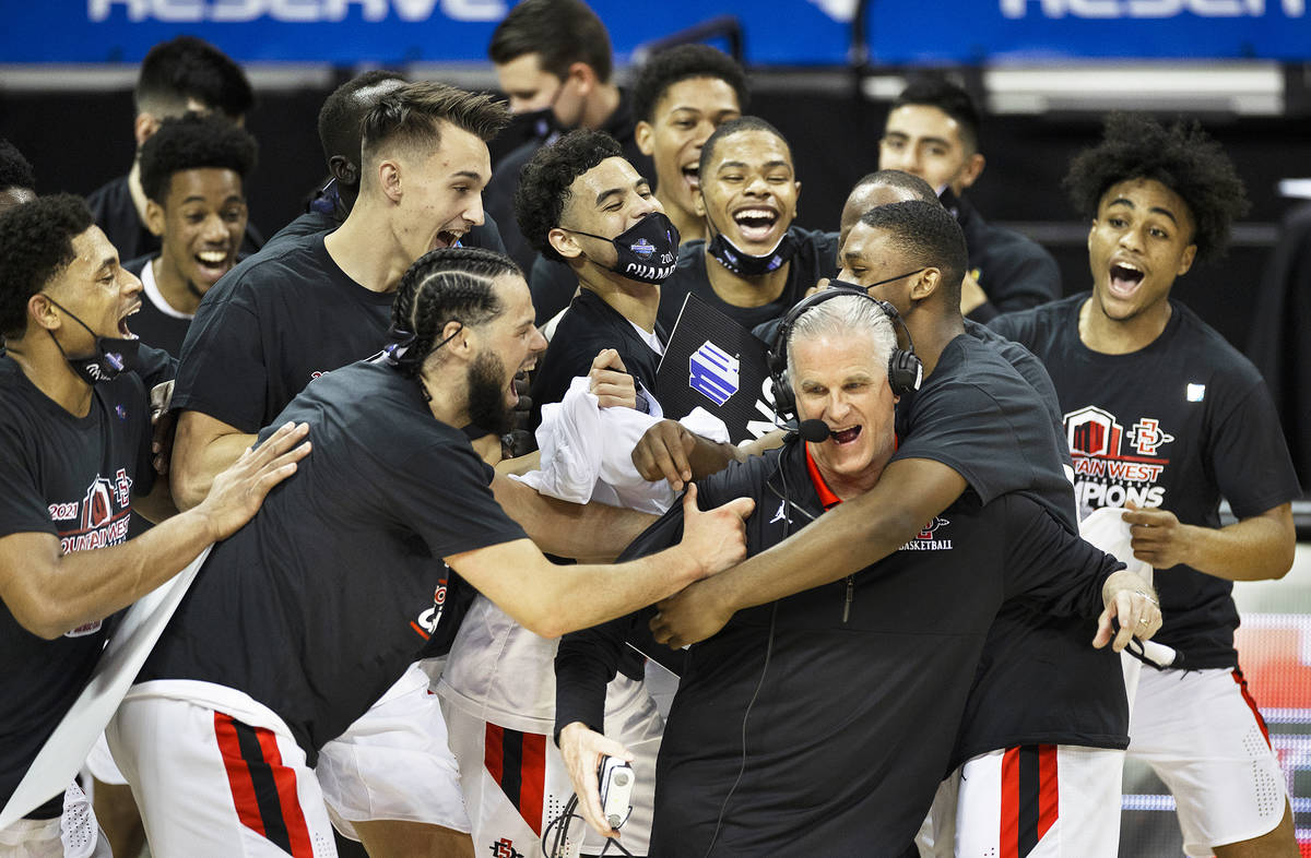 San Diego State Aztec players celebrate with San Diego State Aztecs head coach Brian Dutcher, r ...