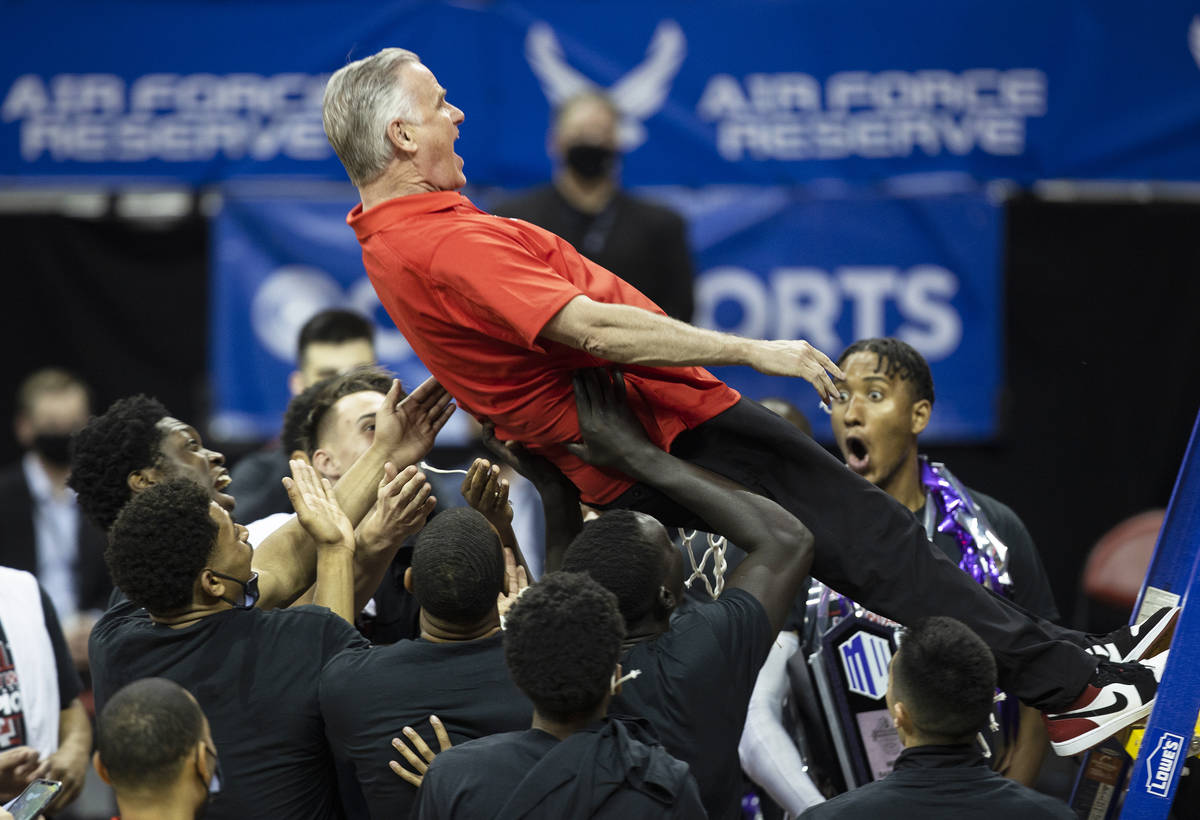 San Diego State Aztecs head coach Brian Dutcher celebrates with a trust fall into his players a ...