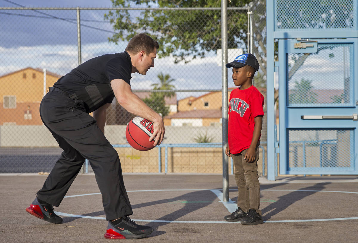 UNLV head basketball coach T.J. Otzelberger, left, teaches Devori Brown, 6, how to dribble duri ...