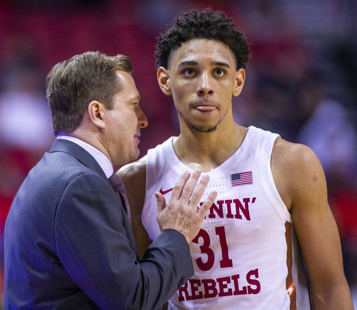 UNLV Rebels head coach T. J. Otzelberger confers with UNLV Rebels guard Marvin Coleman (31) on ...