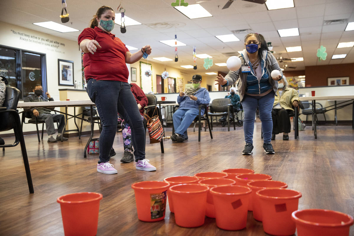 Lead program assistant Samantha Molloy, left, watches as Lani Reardon, 61, throws a ball during ...