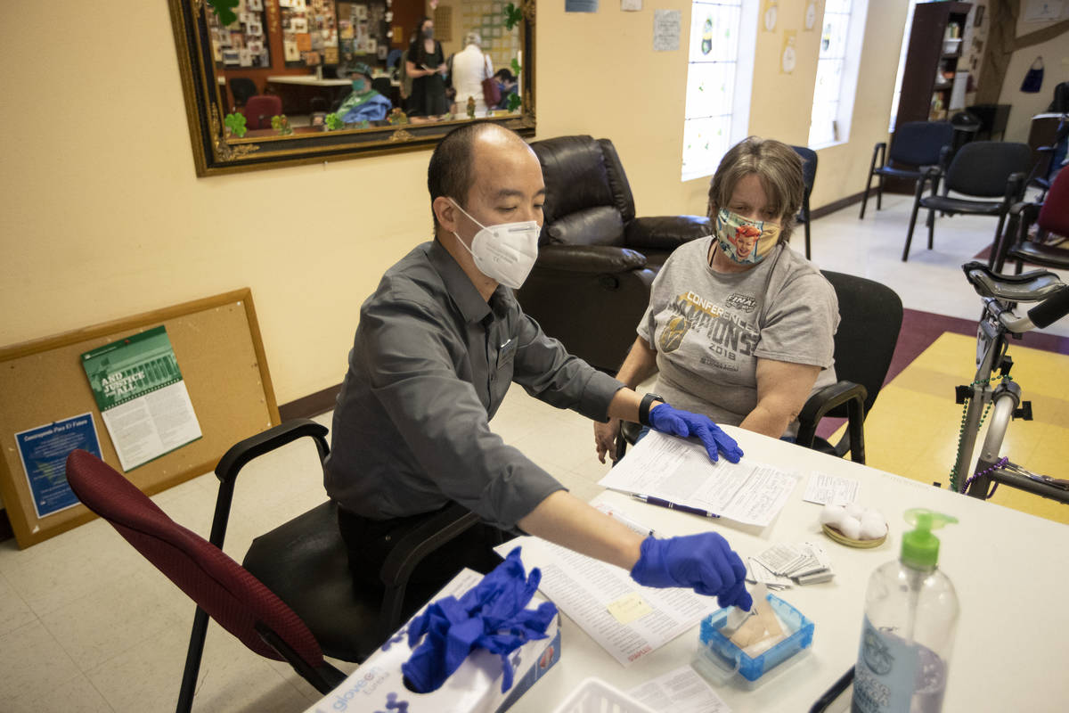Alex Vong, left, pharmacy manager at Albertsons, gets ready to administer the second dose of th ...