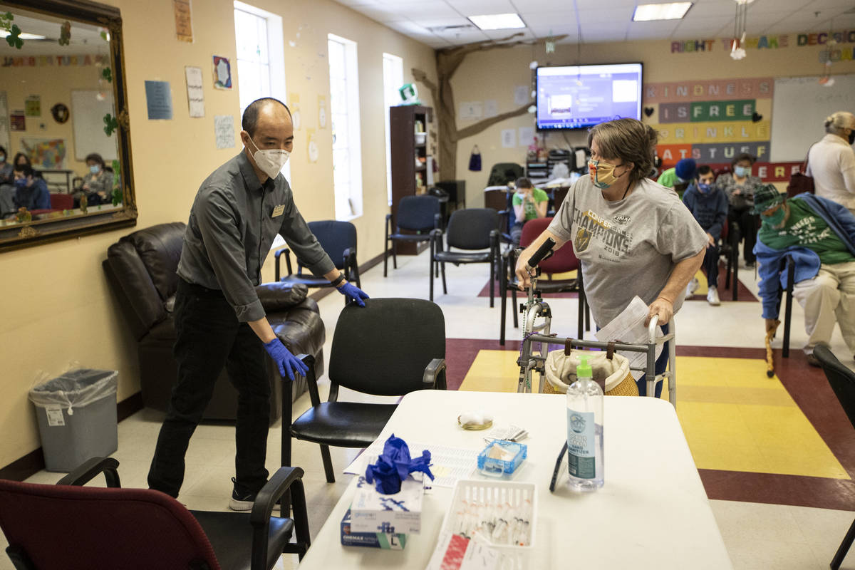 Alex Vong, left, pharmacy manager at Albertsons, assists Elaine Triplett to a chair to receive ...