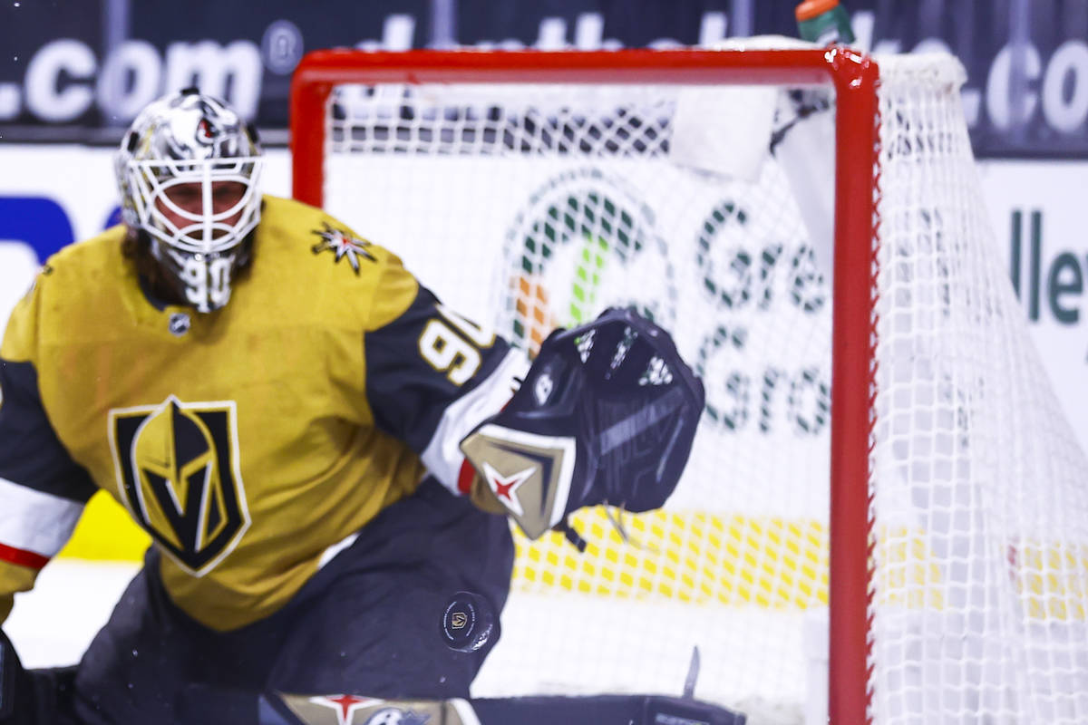 The puck flies past Golden Knights goaltender Robin Lehner (90) during the first period of an N ...