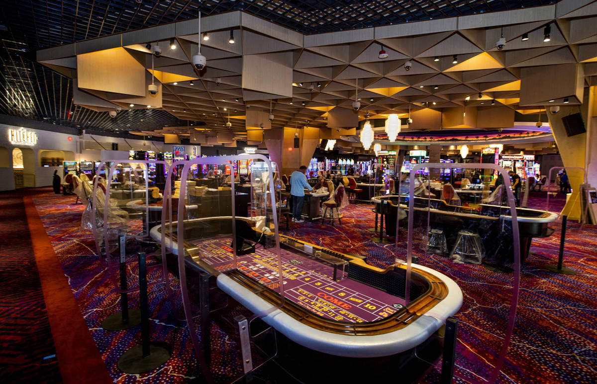 Much plexiglass will keep visitors separated between slots and table games in the main gambling ...