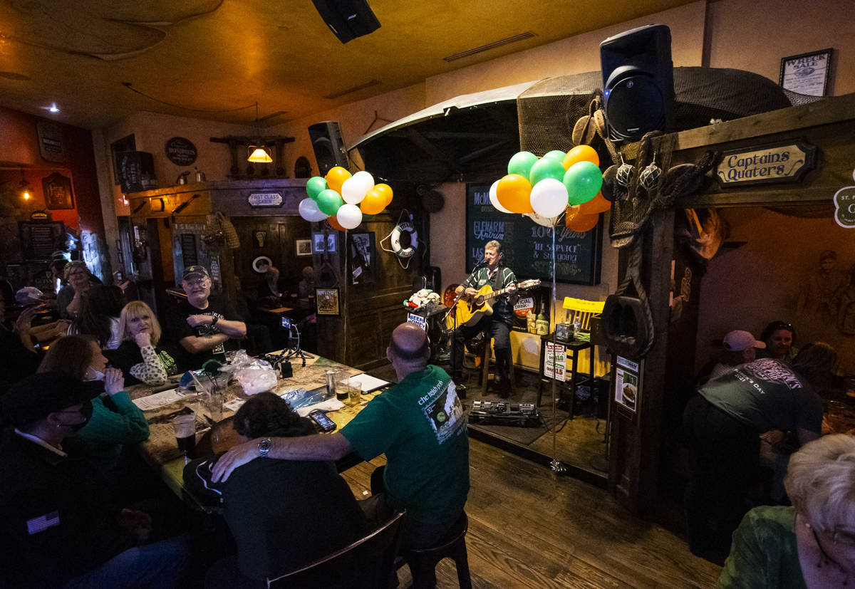 Musician John Windsor performs as people gather to celebrate St. Patrick's Day at McMullan's Ir ...