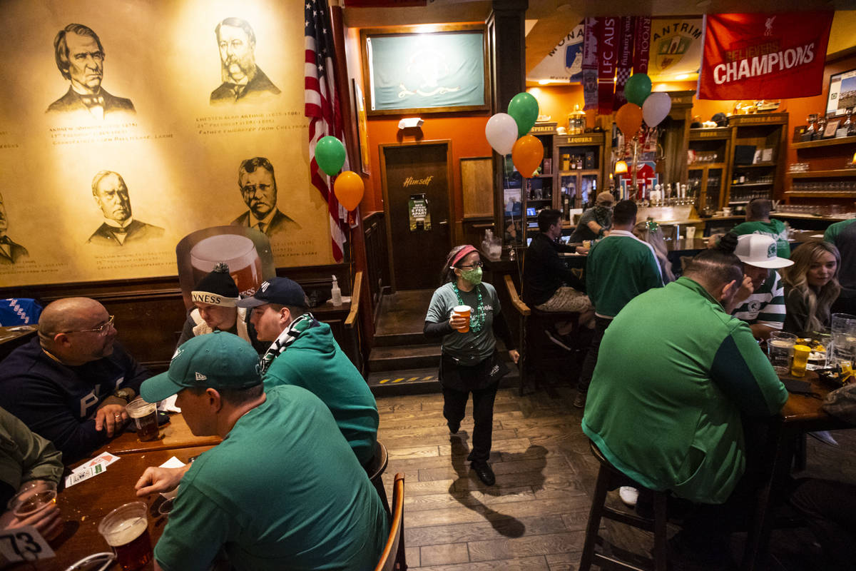 Jennifer Calabrese, right, serves drinks as people gather to celebrate St. Patrick's Day at McM ...