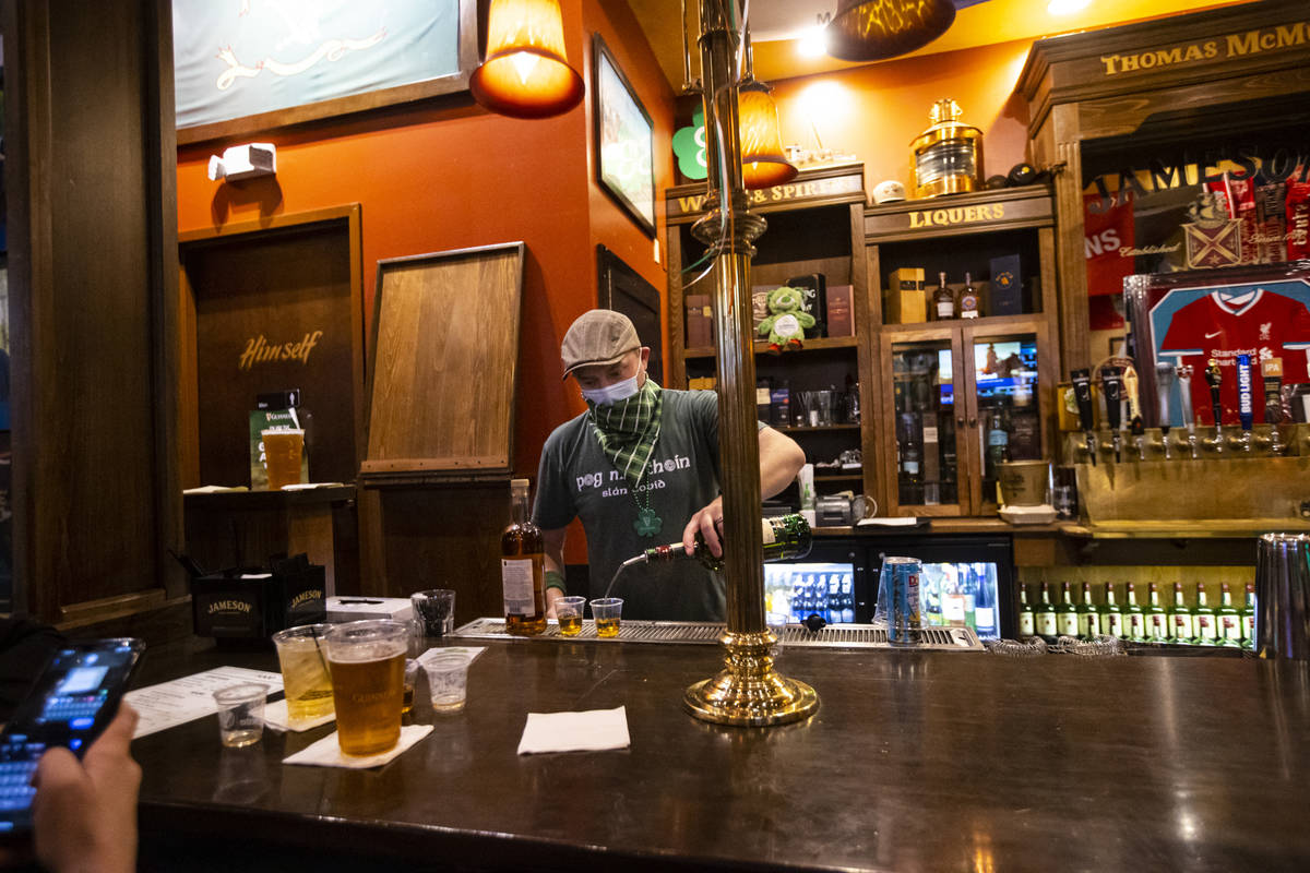 Bartender Paul Walsh Jr. prepares drinks as people gather to celebrate St. Patrick's Day at McM ...