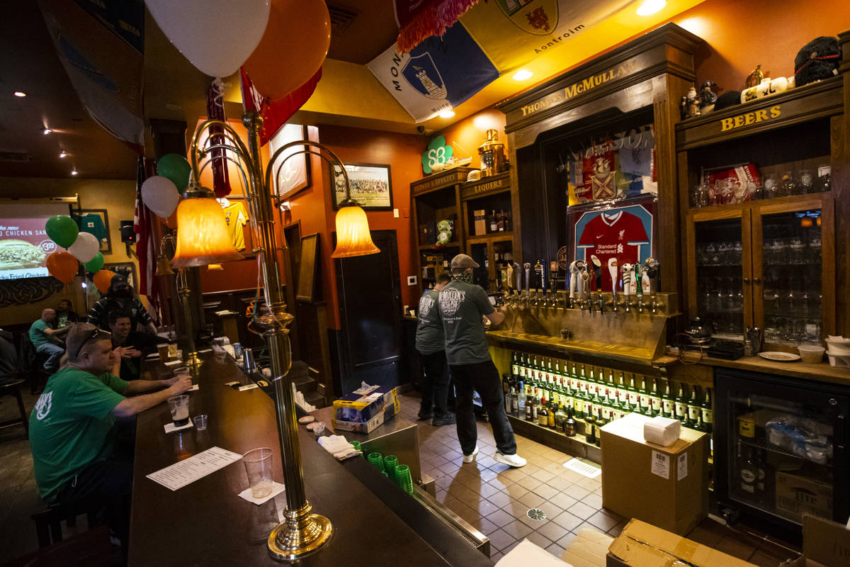 Bartender Paul Walsh Jr., right, prepares drinks as people gather to celebrate St. Patrick's Da ...
