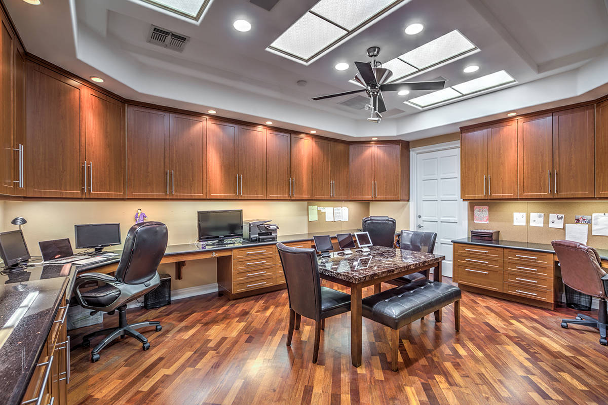 The home has a collaborative workspace that has five granite-topped computer stations and cente ...