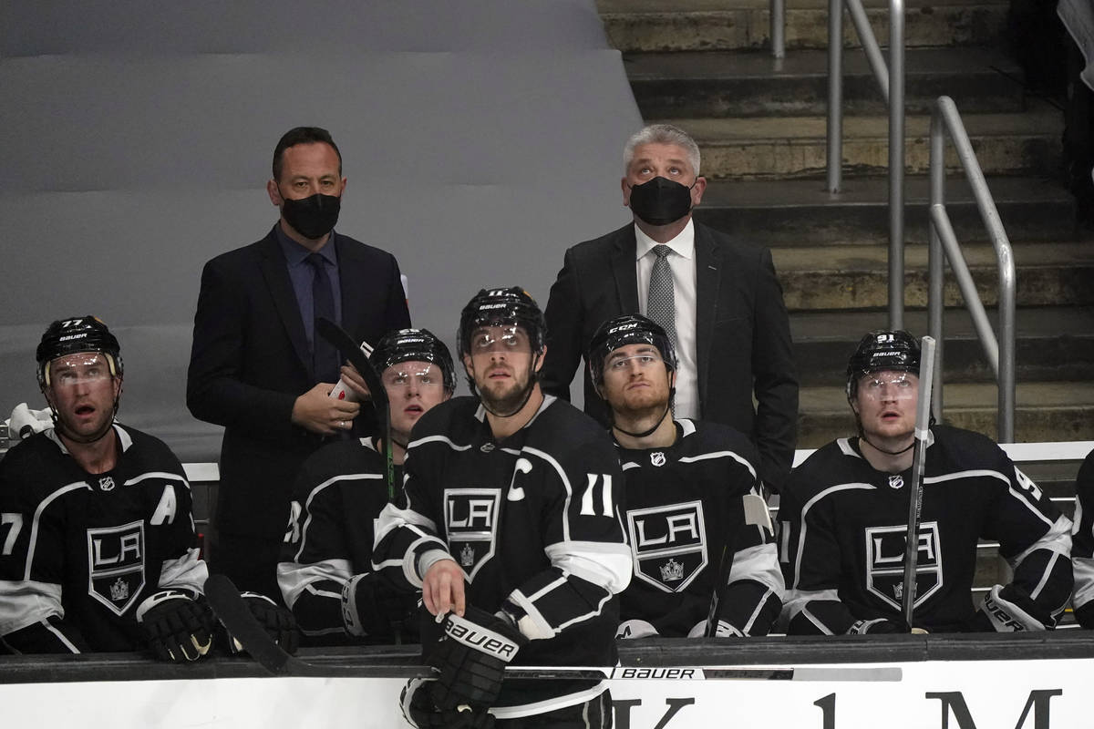 Los Angeles Kings coach Todd McLellan, back right, looks up at the screen during a break in the ...