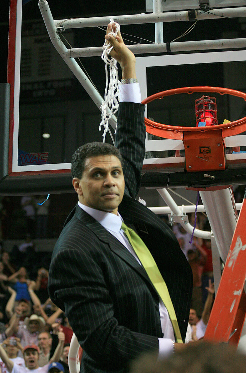 New Mexico State coach Reggie Theus cuts down the net after his team defeated Utah State 72-70 ...