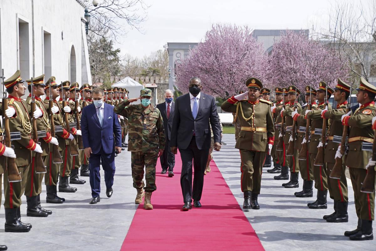 U.S. Defense Secretary Lloyd Austin, center, walks on the red carpet with Acting Afghan Ministe ...