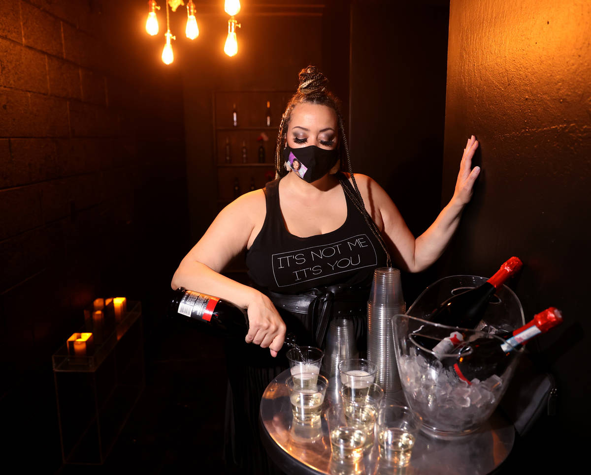 Sydni Sayles pours sparkling wine for guests arriving on reopening night at Cork and Thorn in d ...