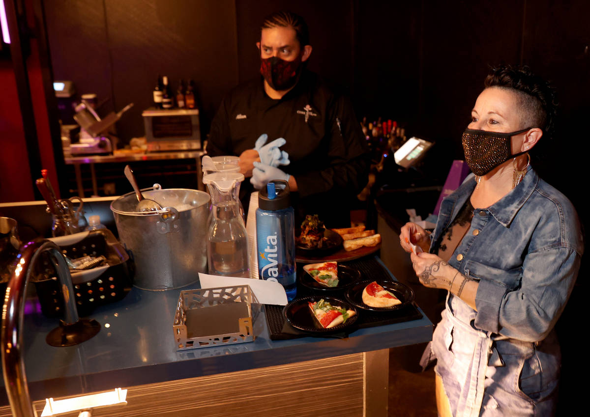 Owner Randi Garrett and Allan Garay prepare to deliver food orders on reopening night at Cork a ...