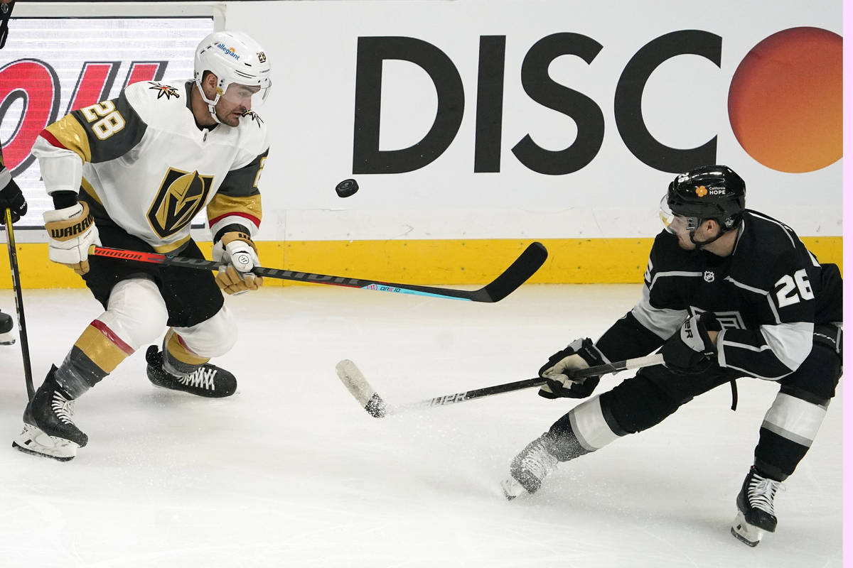 Vegas Golden Knights left wing William Carrier, left, tries to knock the puck out of the air wh ...