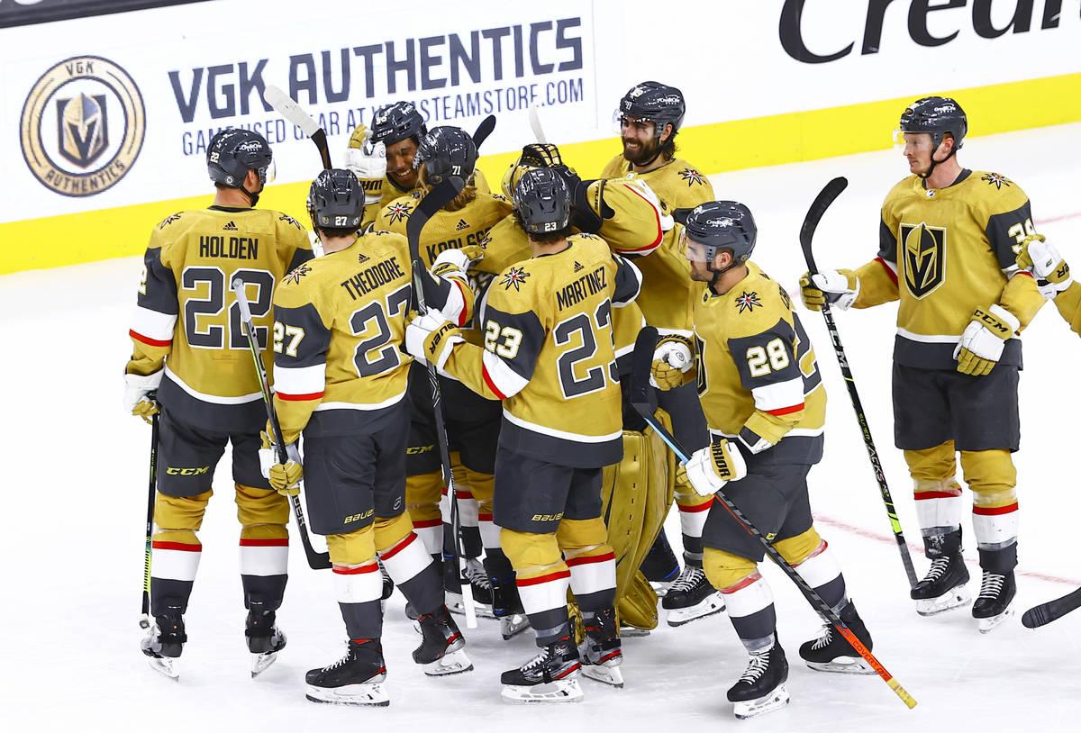 Golden Knights' Keegan Kolesar, upper left, celebrates with teammates after a hockey game where ...