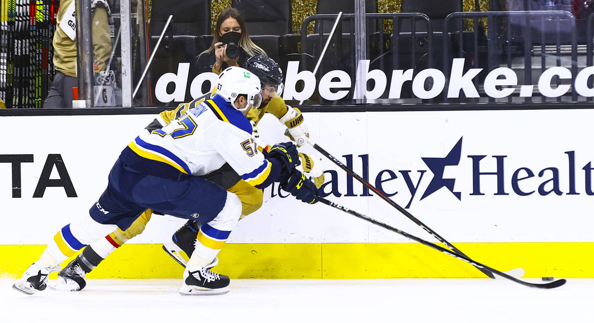 St. Louis Blues' David Perron (57) and Golden Knights' Alex Tuch (89) battle for the puck durin ...