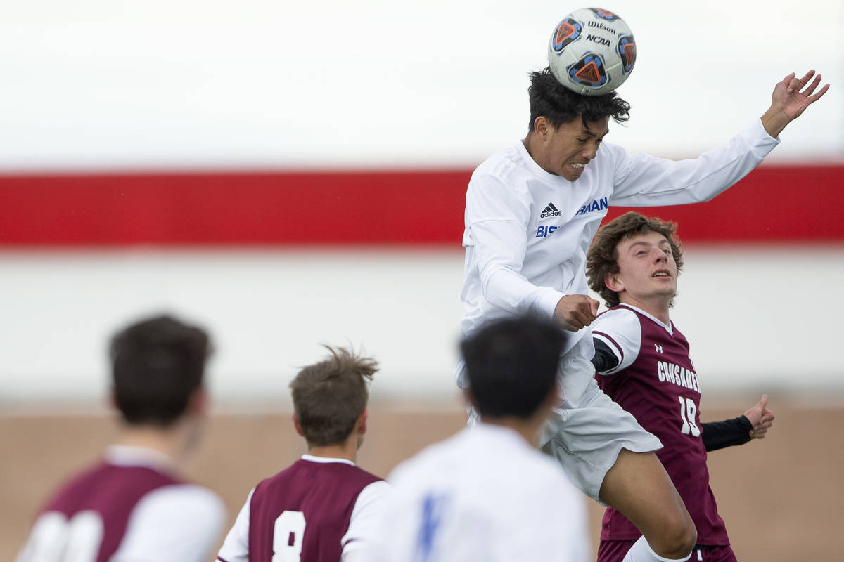 Bishop Gorman defender George Charles (15), left, heads the ball as Faith Lutheran forward Jere ...