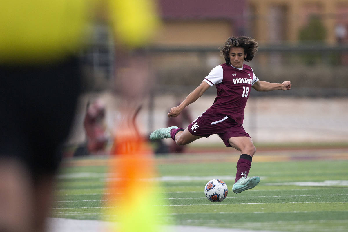 Faith Lutheran defender Logan Renteria (12) winds up to pass during a high school soccer game a ...