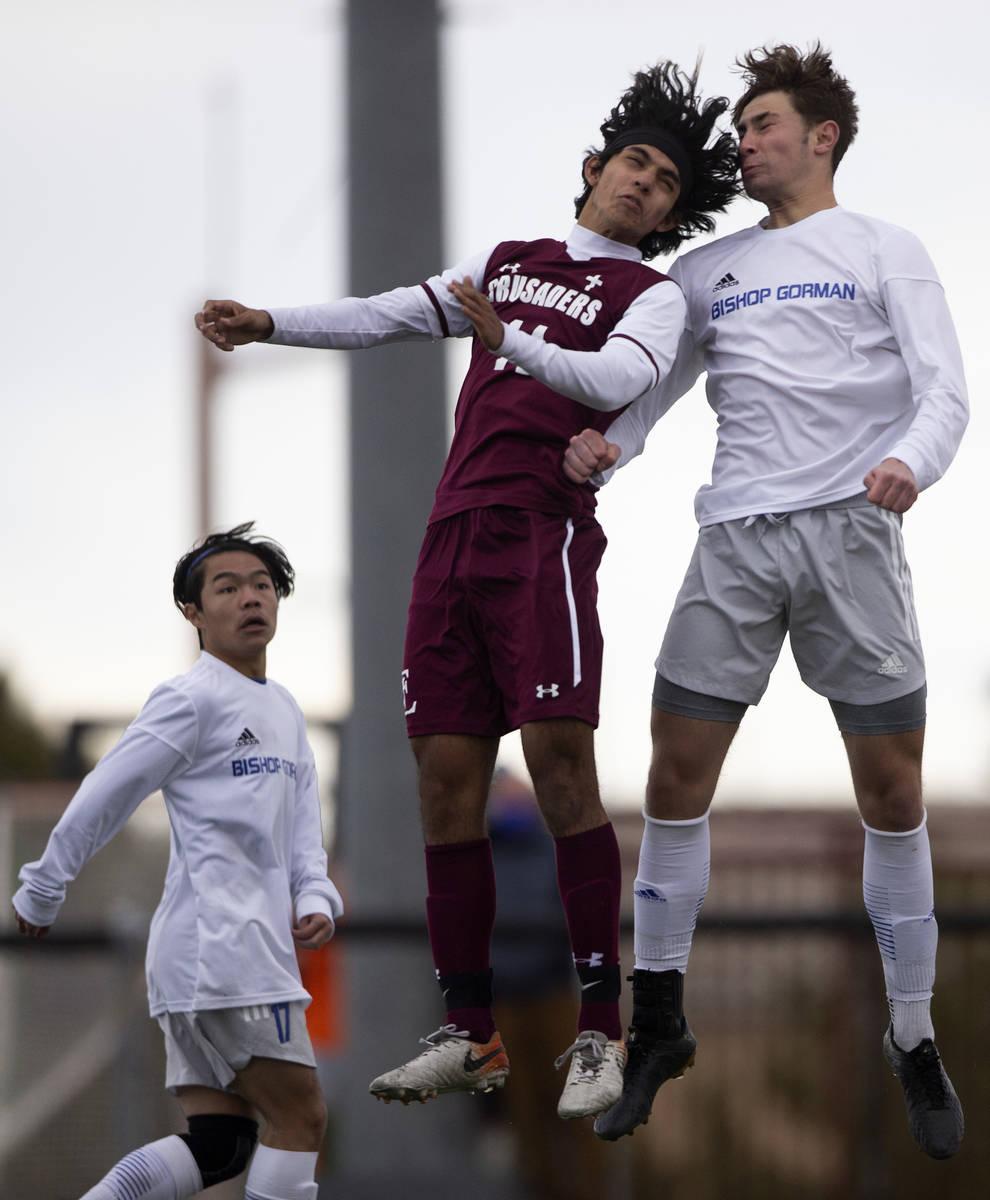 Faith Lutheran forward Ari Sirvent (14) and Bishop Gorman defender Keegan Brooks (4) jump for a ...