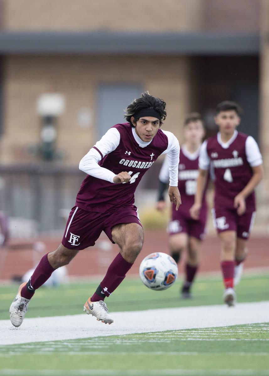 Faith Lutheran forward Ari Sirvent (14) eyes the ball during a high school soccer game against ...
