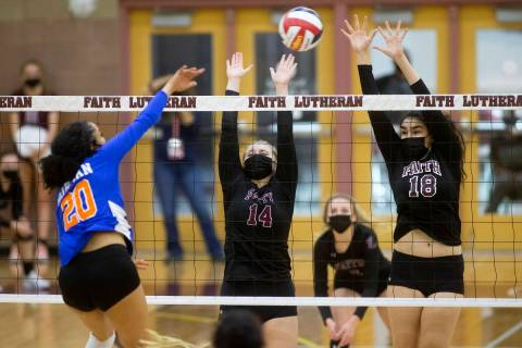 Bishop Gorman's Sophia Ewalefo (20) spikes while Faith Lutheran's Ella Runstad (14) and Haylee ...