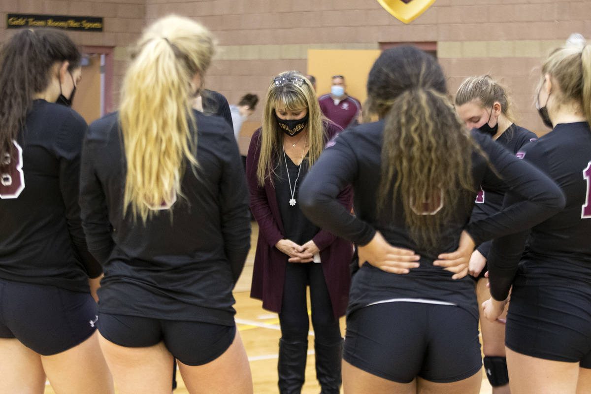 Faith Lutheran's head coach Amy Fisher leads a prayer after the team lost a high school volleyb ...