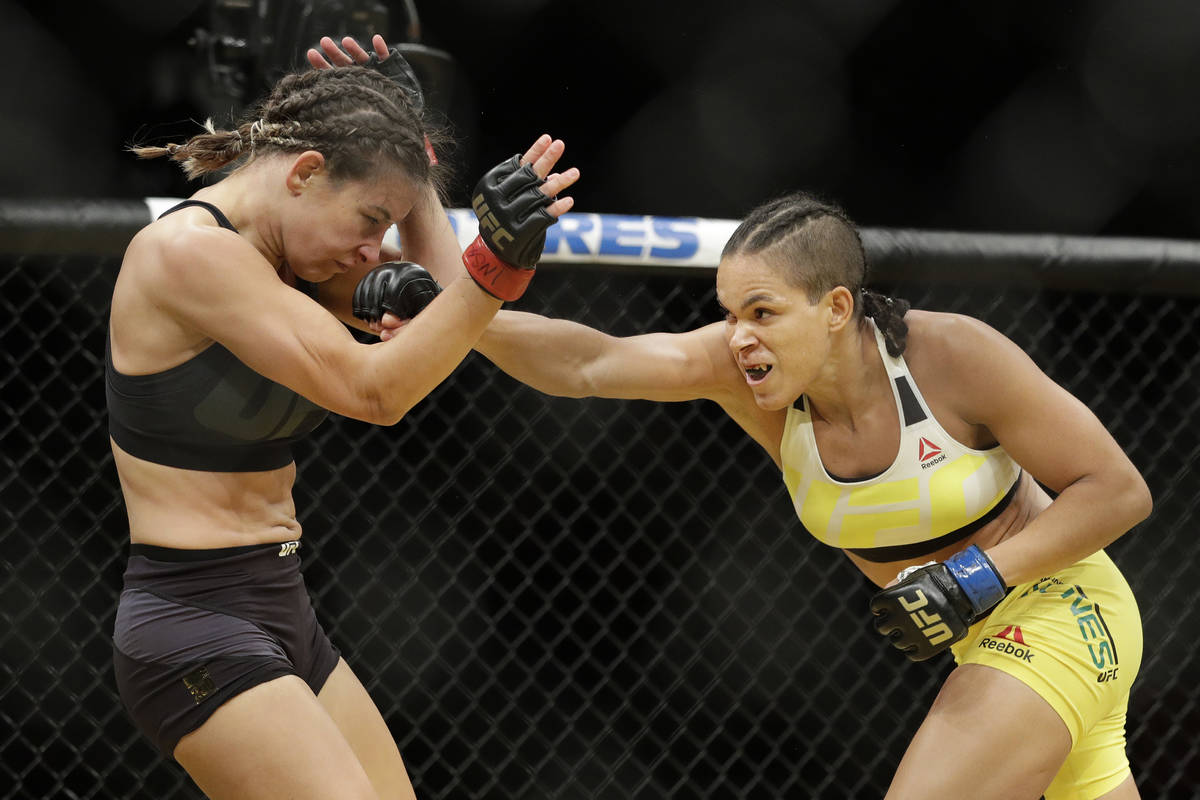 Amanda Nunes, right, hits Miesha Tate during their women's bantamweight championship mixed mart ...