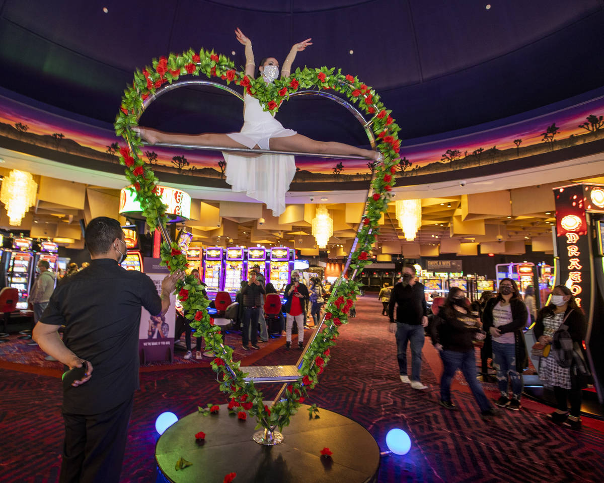 Aerialist Svetlana Ghetman spins on a rotating heart within the middle of the casino floor duri ...