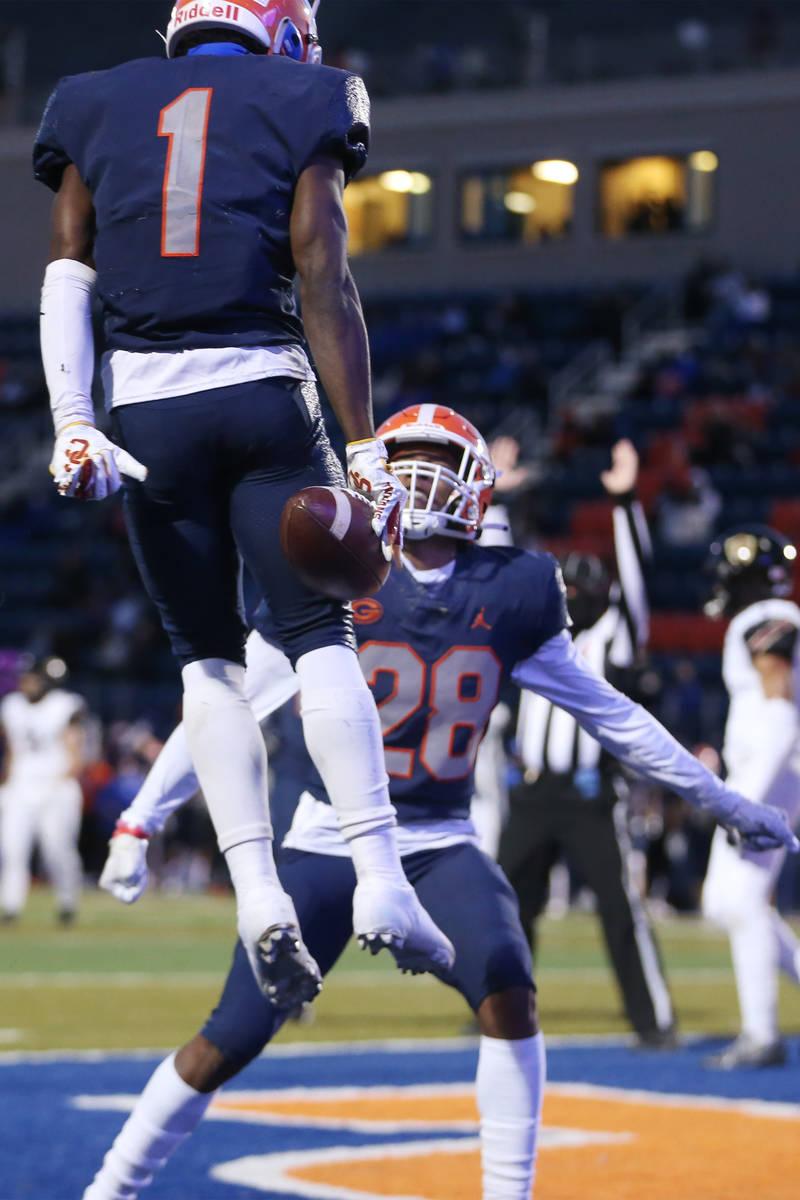 Bishop Gorman's Zachariah Branch (1) celebrates his touchdown with teammate Jeremiah Hughes (28 ...