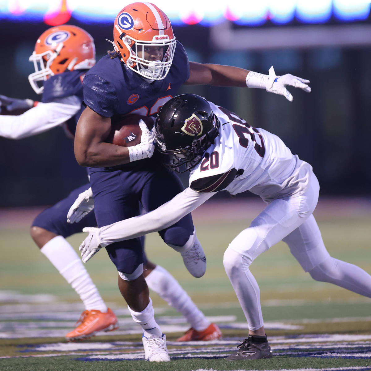 Bishop Gorman's Sebastian Shannon (23) is tackled by Faith Lutheran's Chandler Silva (20) durin ...