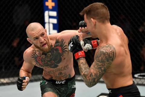 Conor McGregor of Ireland punches Dustin Poirier in a lightweight fight during the UFC 257 even ...