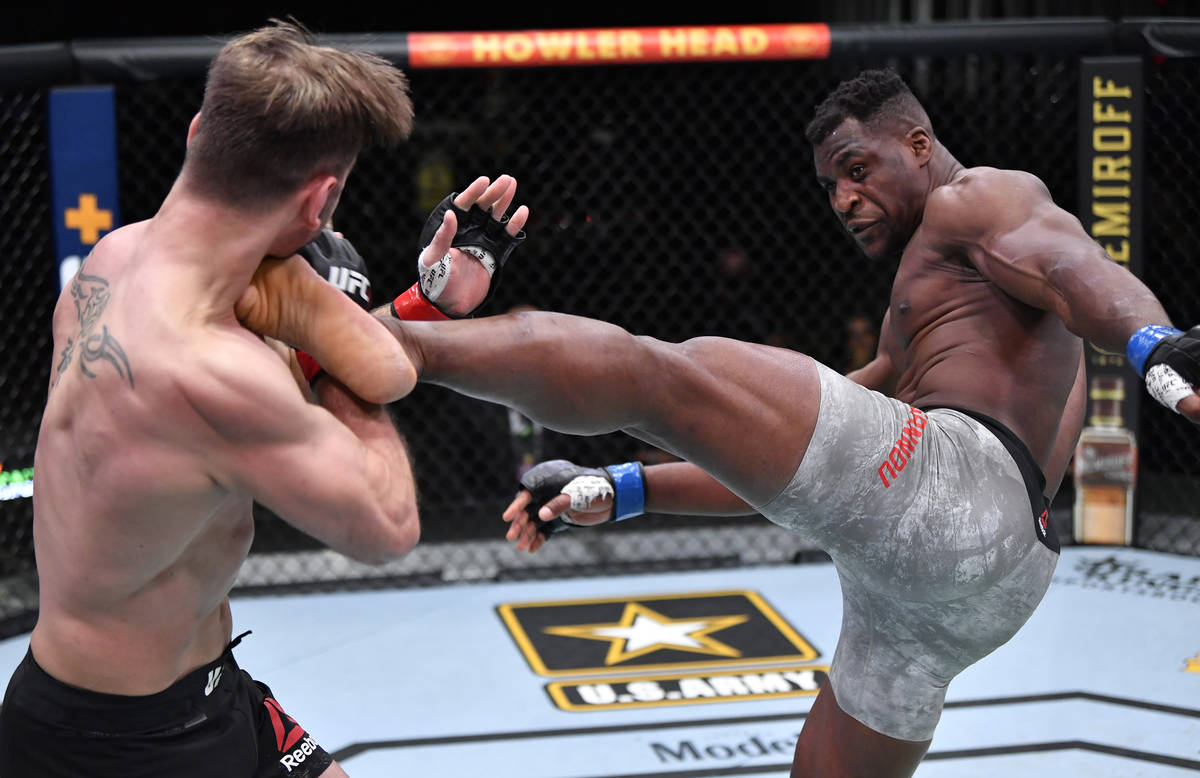 LAS VEGAS, NEVADA - MARCH 27: (R-L) Francis Ngannou of Cameroon kicks Stipe Miocic in their UFC ...