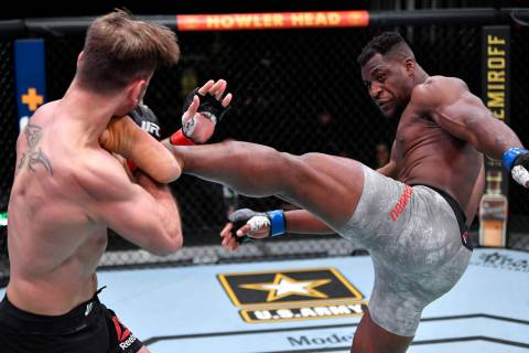 Francis Ngannou of Cameroon kicks Stipe Miocic in their UFC heavyweight championship fight duri ...