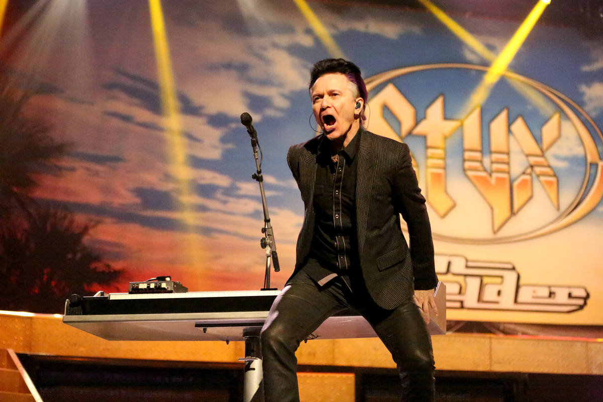 Lawrence Gowan of Styx plays the keyboard behind his back during a performance of the Styx hit, ...