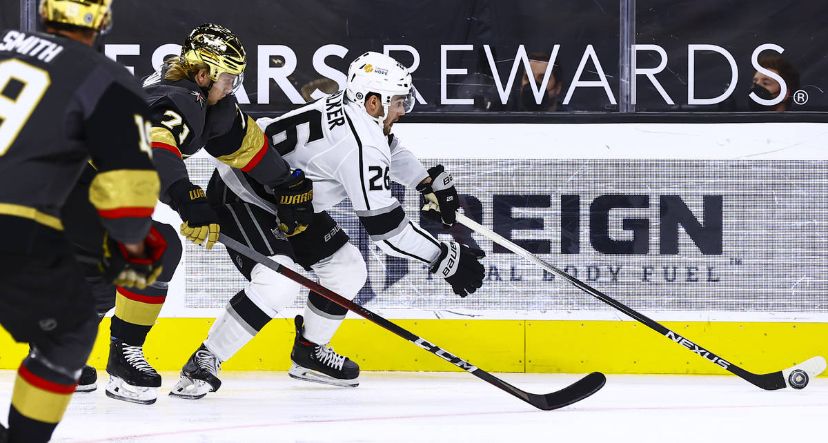 Los Angeles Kings' Sean Walker (26) skates with the puck under pressure from Golden Knights' Wi ...