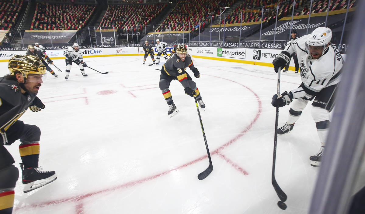 Los Angeles Kings' Anze Kopitar (11) passes the puck under pressure from Golden Knights' Brayde ...
