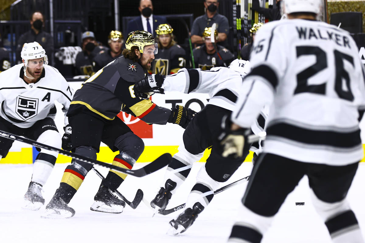 Golden Knights' Mark Stone (61) skates with the puck past Los Angeles Kings' Jeff Carter (77) a ...