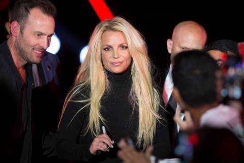Britney Spears signs an autograph during an event to announce her residency at The Park Theater ...