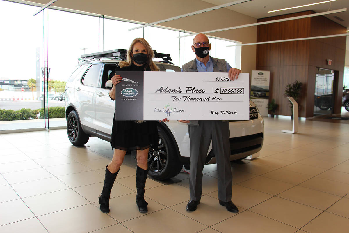 Kelly Thomas-Boyers, president of Adam's Place, accepts a donation check for $10,000 from Ray ...