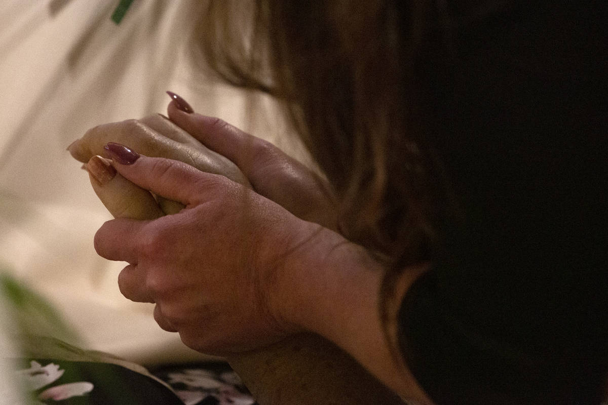 Renae Swartz holds her mother's hand while she lays in her casket. The family is split between ...