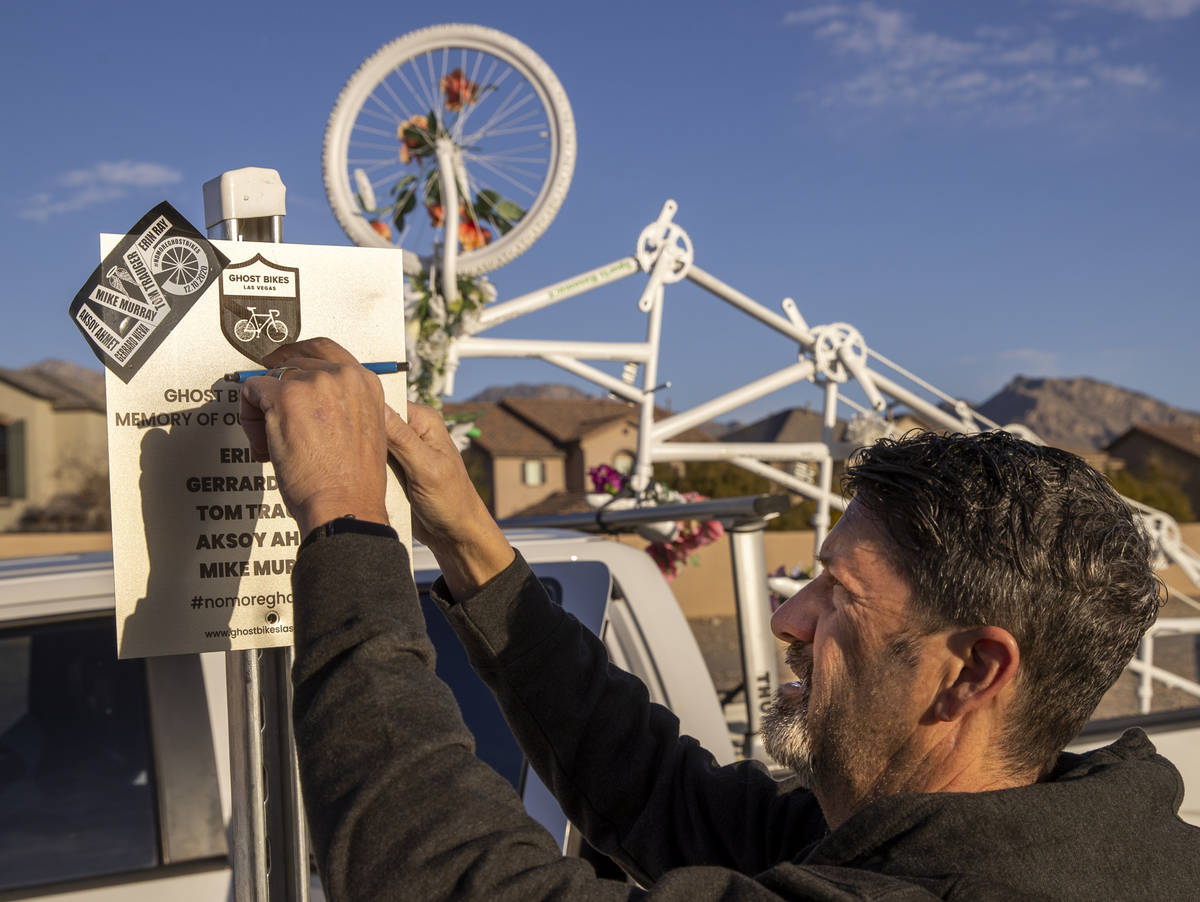 Pat Treichel with Ghost Bikes Las Vegas removes a plaque as they relocate their 5-person bike f ...