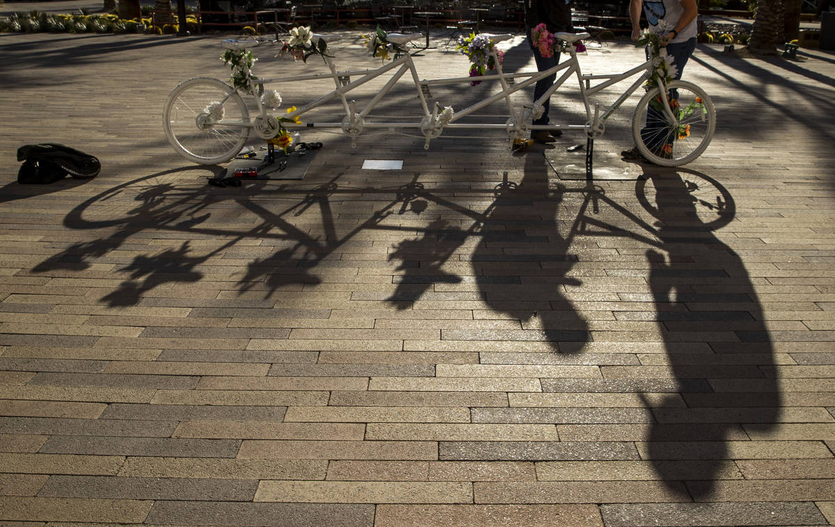 Shadows of Pat Treichel, left, and Steve White with Ghost Bikes Las Vegas as they relocate thei ...