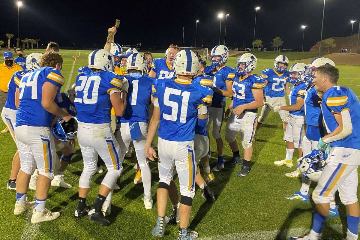 Moapa Valley coach Brent Lewis celebrates with the hammer as players circle around after the Pi ...