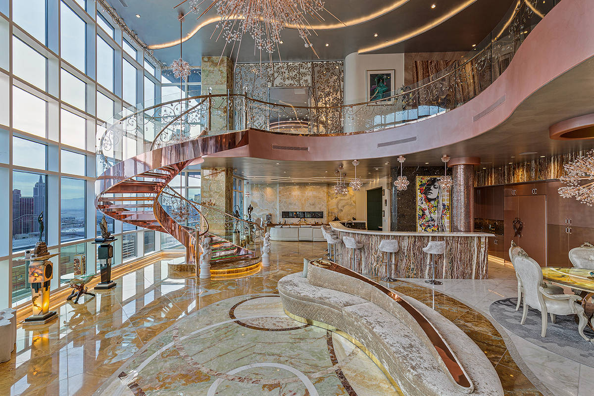 A rose-gold lighted glass and crystal circular floating staircase is the focal point of the gr ...