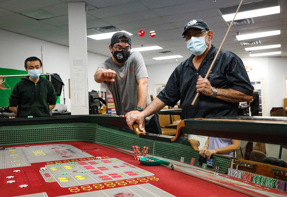 Bruce Lin, from left, plays craps with Marc Heslet, center, and dice coach Ronnie Binkier, righ ...