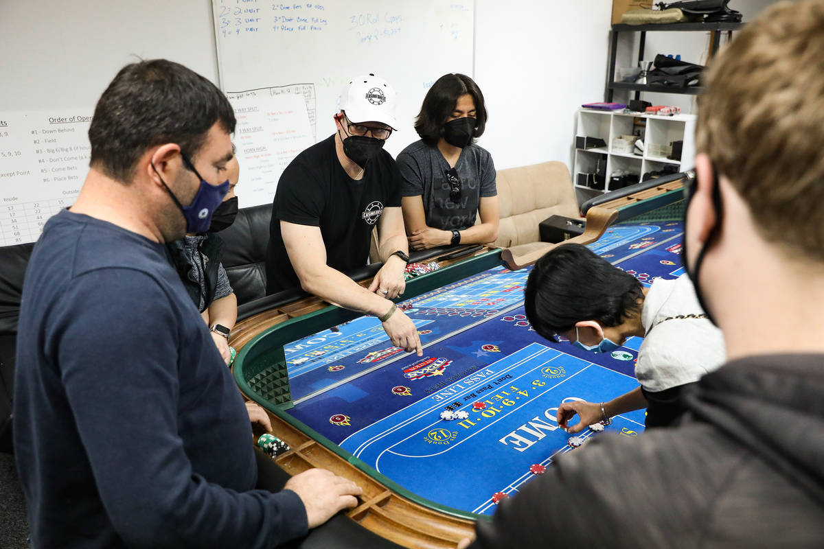 David Noll, managing director for CEG Dealer School, center, teaches students how to play craps ...
