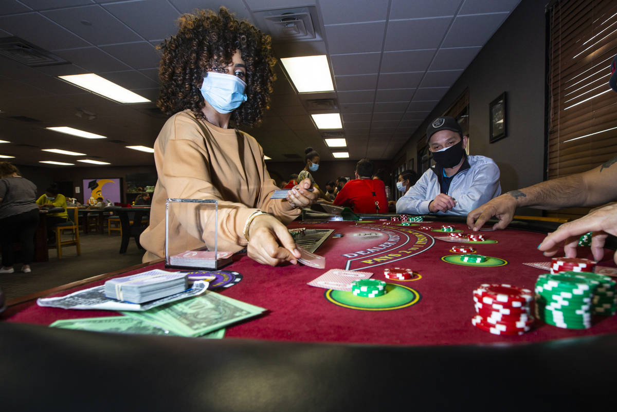 Instructor Yodit Girma, left, deals cards while working a blackjack table with students, includ ...