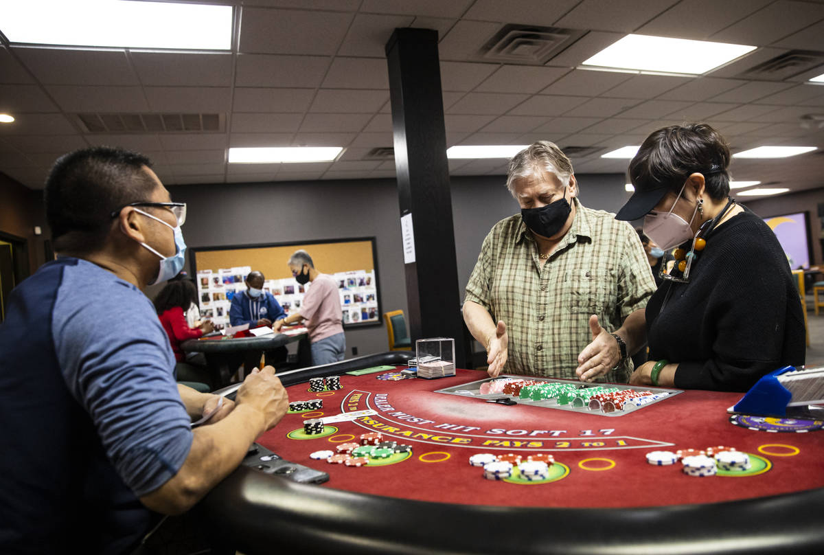 Instructor Ray Nichols, center, assists students Steven Chen, left, and Grace Ho at a blackjack ...